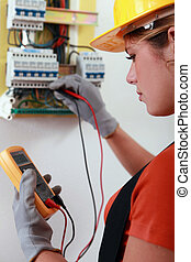 Female electrician checking the wiring on a fusebox