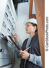 female electrician checking voltage of the electric power switch