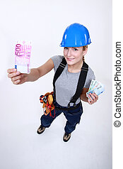 Female electrician holding money