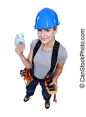 Female electrician holding wedge of cash