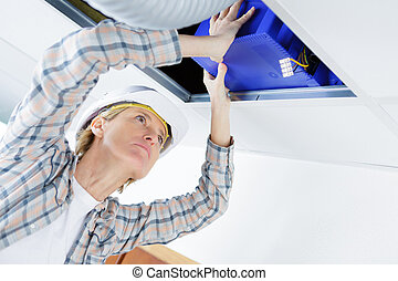 female electrician installing electric device in ceiling