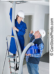 female electrician installing ventilation pipese in ceiling