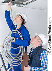 female electrician installing wires in ceiling
