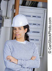 female electrician standing in front of open fuse box