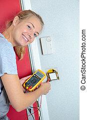 Female electrician using multi meter