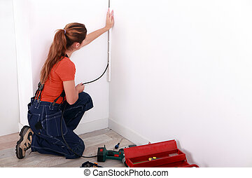 Female electrician wiring a white room