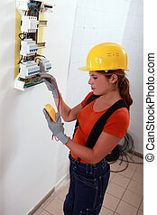 Female electrician with a fuse box