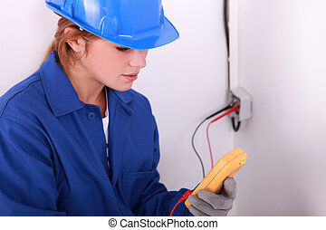 Female electrician with a multimeter