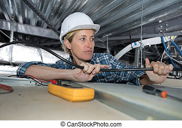 Female electrician working in confined space