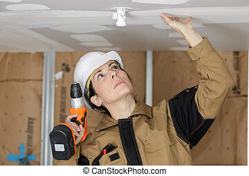 female electrician working in home