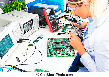 Female electronic engineer checking circuit board in...