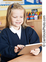 Female Elementary School Pupil Using Digital Tablet In Class