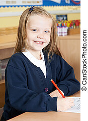Female Elementary School Pupil Working At Desk