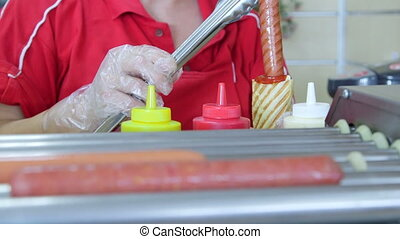 Female employee making hotdog in takeout diner close-up