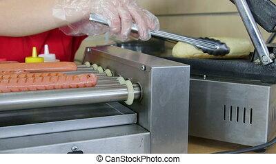 Female employee making hotdogs heating bun in fast food lunch dinner
