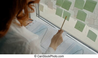 Female employee working with blueprint, standing by window with sticky in company.
