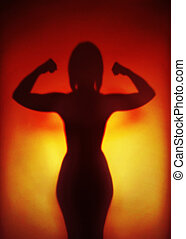 female empowerment or feminism or emancipation concept, silhouette of an anonymous strong woman flexing muscles