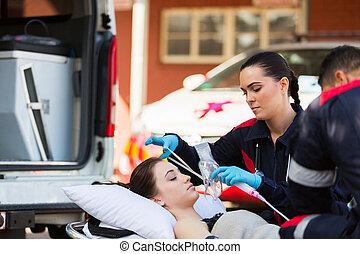 female EMT putting oxygen mask on patient - young female EMT...