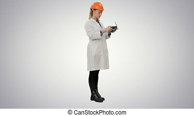 Female engineer correct parts of an object using remote controller on white background.