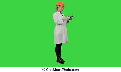 Female engineer correct parts of an object using remote controller on a Green Screen, Chroma Key.