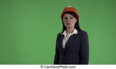 Female engineer in safety helmet making presentation against a green screen