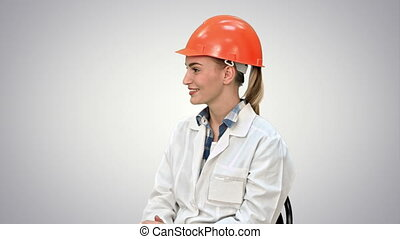 Female engineer in safety helmet sitting and talking on white background.
