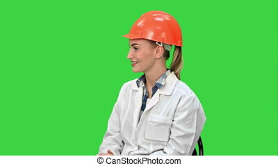 Female engineer in safety helmet sitting and talking on a Green Screen, Chroma Key.