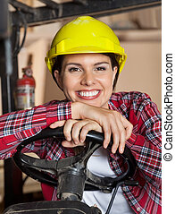 Female Engineer Leaning On Forklift's Steering Wheel