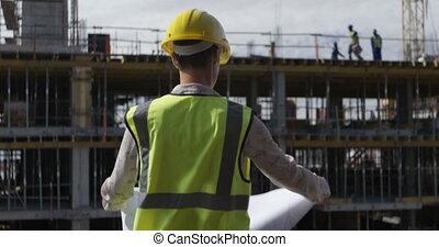 Female engineer looking at blueprint 4k