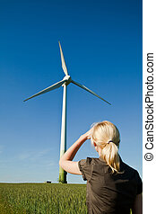 Female engineer looks at wind turbine - alternative and green energy source