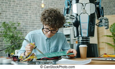 Female engineer attractive girl is soldering robot motherboard with solderer in modern office concentrated on job. Electronics, people and occupation concept.