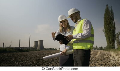 Female engineer supervisor indicating on her colleague on tablet pc weak points and issues of project on industrial platform