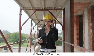 Female Engineer Talking On Mobile Telephone In Construction Site