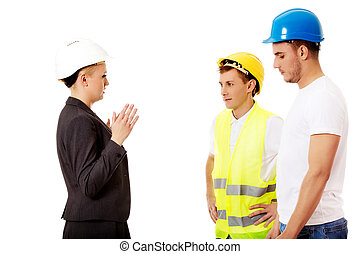 Female engineer talking with two builders