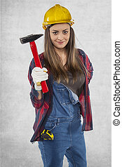 Female engineer with a hammer in her hand