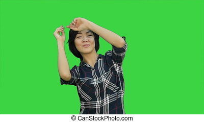 Female engineer with a jrange hemlet and construction plan trying to talk with somebody far away on a Green Screen, Chroma Key