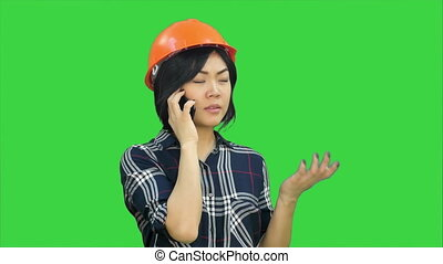 Female engineer with orange helmet having a phone call via smartphone on a Green Screen, Chroma Key