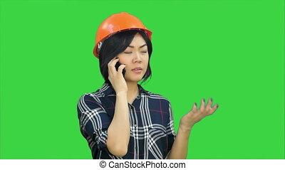 Female engineer with orange helmet having a phone call via...