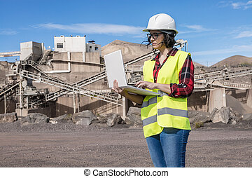 Female engineer working with laptop on construction site