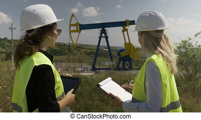 Female engineering specialists coworkers using digital tablet and clipboard discussing about development strategy of oilfield industry