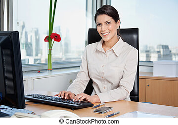 Female Entrepreneur Working On Computer - Portrait of...