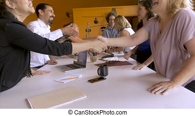 Female entrepreneurs shaking hands with investors during a collaborative meeting