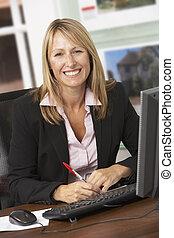 Female Estate Agent Working At Desk