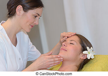 female esthetician massaging head and face of young woman