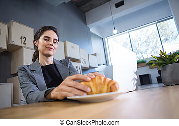 Female executive having croissant at table