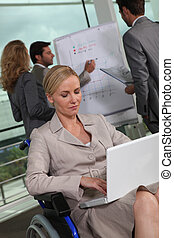Female executive in wheelchair using laptop computer
