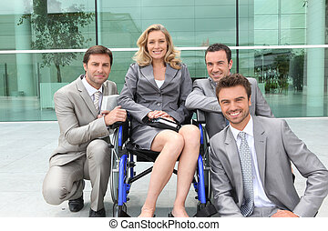 Female executive in wheelchair with colleagues outside office building