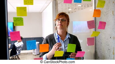 Female executive looking on sticky note on glass wall 4k -...