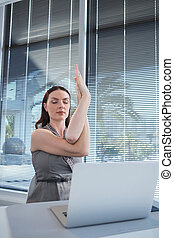 Female executive performing yoga at desk in office