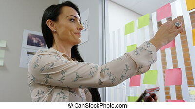 Female executive removing sticky note while using digital ...